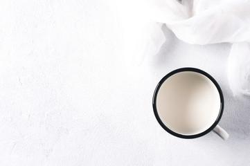 Milk in an iron mug on a white concrete background
