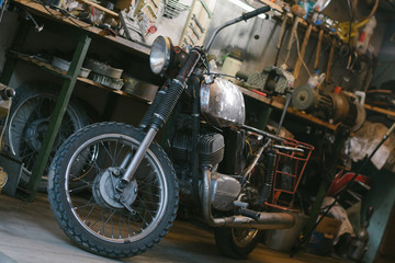 Old vintage motorcycle, which needs to be repaired, in the workshop