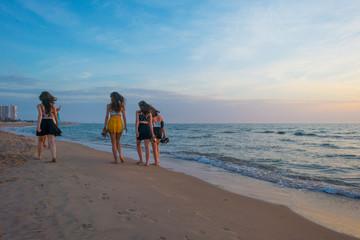 Girls walking on a beach along the sea at sunrise