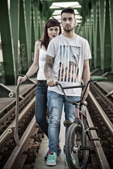 Young couple with skateboard and BMX bicycle outdoors