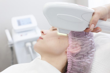 Woman getting laser face treatment in medical spa center