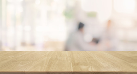 Wood table top and blurred restaurant kitchen interior background - can used for display or montage your products.
