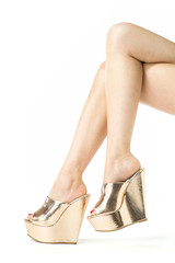 Legs with high heels mules in metallic gold