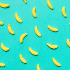 sweets in the shape of bananas on a blue background. minimal flat lay. party food