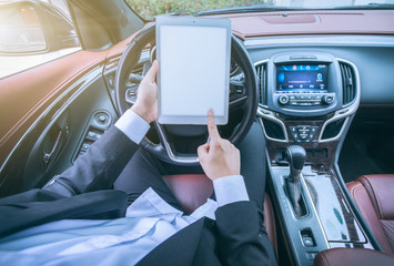 Businessman sit in his car using digital tablet.