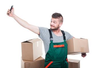 Mover guy holding cardboard box taking selfie