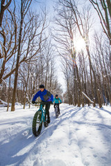 Attractive couple riding fat bikes in the snow