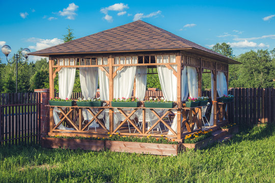 Outdoor wooden gazebo with flowers and summer landscape background