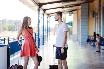Happy caucasian couple standing with the suitcases at the train station, talking and looking at each other. Taken at summer daytime.