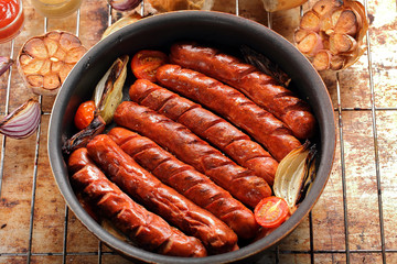 Grilled sausages in oven pan with garlic and onion