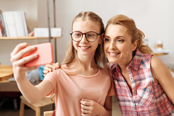 Sweet mother and daughter posing for a selfie