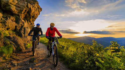Mountain biking women and man riding on bikes at sunset mountains forest landscape. Couple cycling MTB enduro flow trail track. Outdoor sport activity. Wall mural