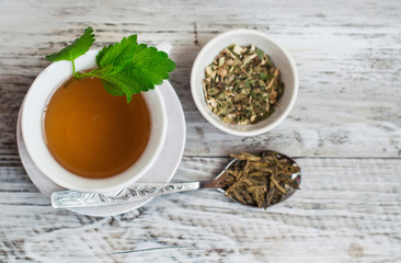 Green tea with mint, drink in a cup close up. On a wooden, light background.