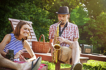 Young man playing saxophone, woman is listening