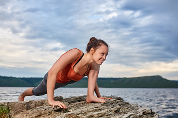 Healthy woman practicing yoga on the rock against beautiful landscape with river.
