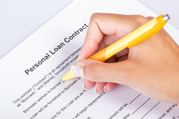 Personal Loan Contract signing, female hand holding a bright yellow pen