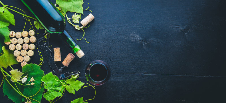 Grape motive. A bottle and a glass of wine and grape leaves. Top view. Free space.