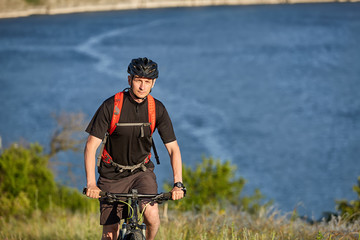 Portrait of the young cyclist riding mountain bike uphill above beautiful blue river.