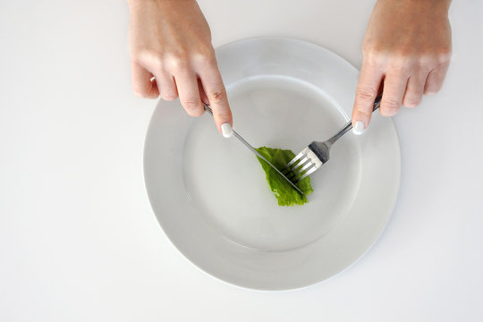 Woman hands eating piece of lettuce