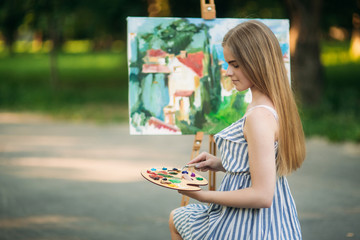 The blonde girl paints a painting on the canvas with the help of paints. A wooden easel keeps the picture.
