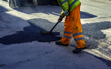 worker leveling fresh asphalt during asphalt pavement repair or construction works