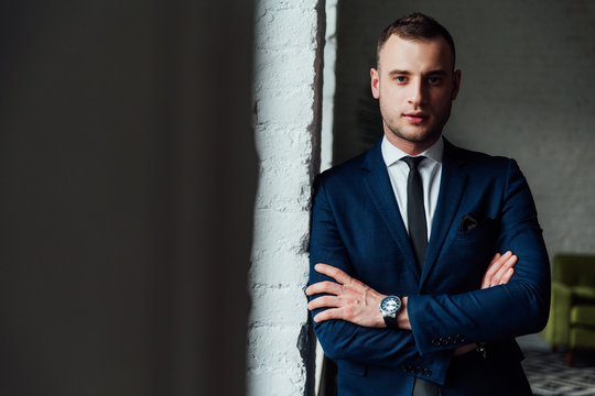Young attractive and confident businessman in blue suit and black tie.
