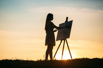 Silhouette of a girl. The blonde girl paints a painting on the canvas with the help of paints. A wooden easel keeps the picture.