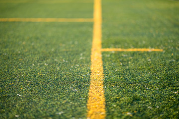 Detail of an artificial turf with yellow lines. Photo with low depth of field.