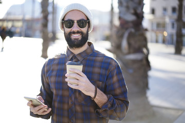 Half length portrait of cheerful bearded guy in trendy sunglasses enjoying sunny weather strolling outdoors with coffee to go,male tourist navigating via application finding location on smartphone
