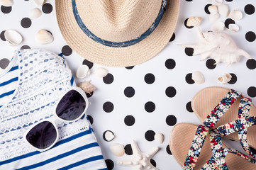Summer women's accessories: sunglasses, hat, sandals, shirt on creative background. Vocations and travel concept top view. Trendy female outfit