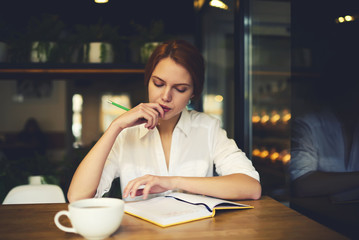 Concentrated young female editor pondering in organizing strategy for project creating plannings sitting in cafe interior, clever marketing expert thinking about developing successful business concept