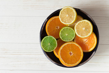 Sliced of lemon, orange and lime in blue ceramic bowl on white wooden table.  Concept healthy food, vegetarian diet.