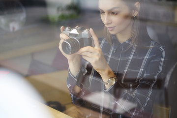Brunette beautiful hipster girl making photo using vintage camera while spending free time indoors.Attractive concentrated woman trying to take good picture while enjoying favorite hobby in cafe