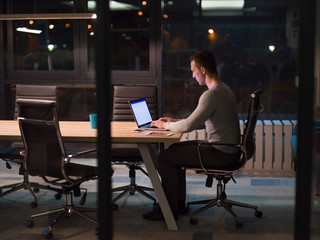 man working on laptop in dark office