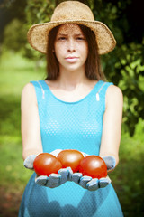 Young woman holding three tomatoes in hands
