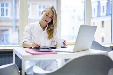Pensive female entrepreneur making notes of working plans while having coffee break in office, charming administrative manager writing strategy planning using laptop computer for making money transfer
