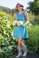 Young woman harvesting pumpkins
