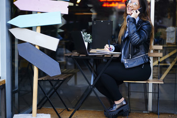 Cheerful female journalist feeling happy getting good news from editor talking on phone working in cafe, attractive smiling hipster girl satisfied with receiving congratulation of successful project