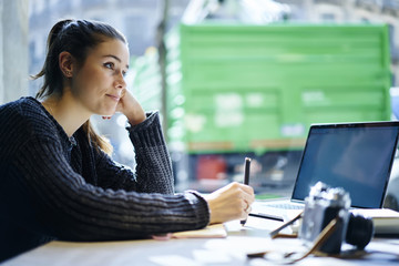 Attractive female student pondering on making report for homework thinking about planning concept in coworking space,hipster girl waiting for feedback updating software on laptop with mock up screen