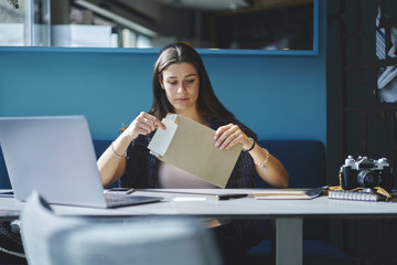 Charming pensive employee of trading company receiving business letter with documentation sitting at working space with laptop computer,concentrate  secretary assistant opening envelope with papers