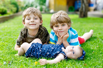 Two little happy kid boys with newborn baby girl, cute sister.