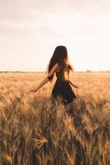 Ragazza vestita di nero che cammina in un campo di spighe di grano