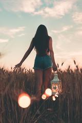Giovane ragazza cammina tra le spighe di grano mentre tiene in mano la lanterna luminosa, al tramonto