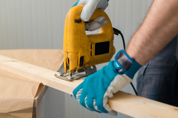 Carpenter handyman using electric handy saw