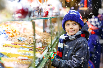 Little kid boy with gingerbread and sweets stand on Christmas market