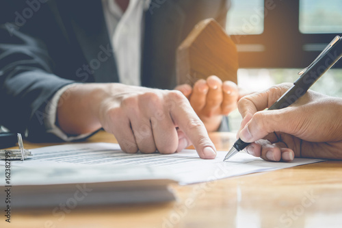 Close Up Of Business Man Pointing And Signing Agreement For Buying