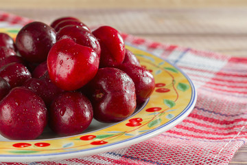 cherries on the table in plate red napkin