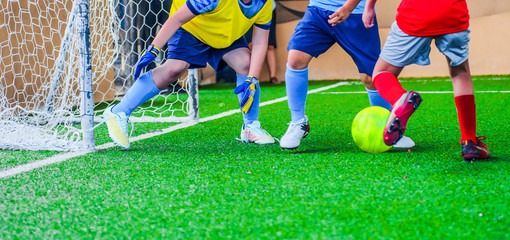 Football tournament - kids playing soccer at artificial pitch, faces hidden