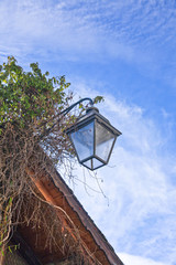 Detail of street lamp hanging on a wooden traditional swiis house with blue sky in background