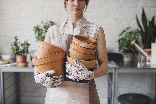 Female florist holding flower pots in workshop